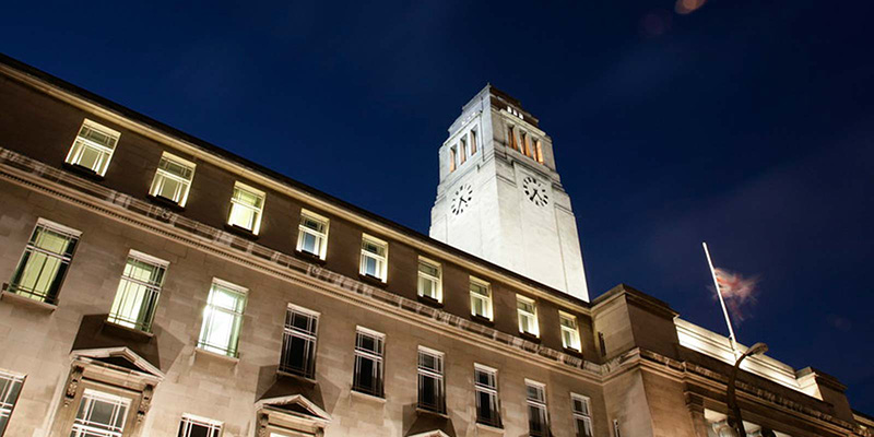 A dramatic upwards shot of the Parkinson building, lit up against a night sky