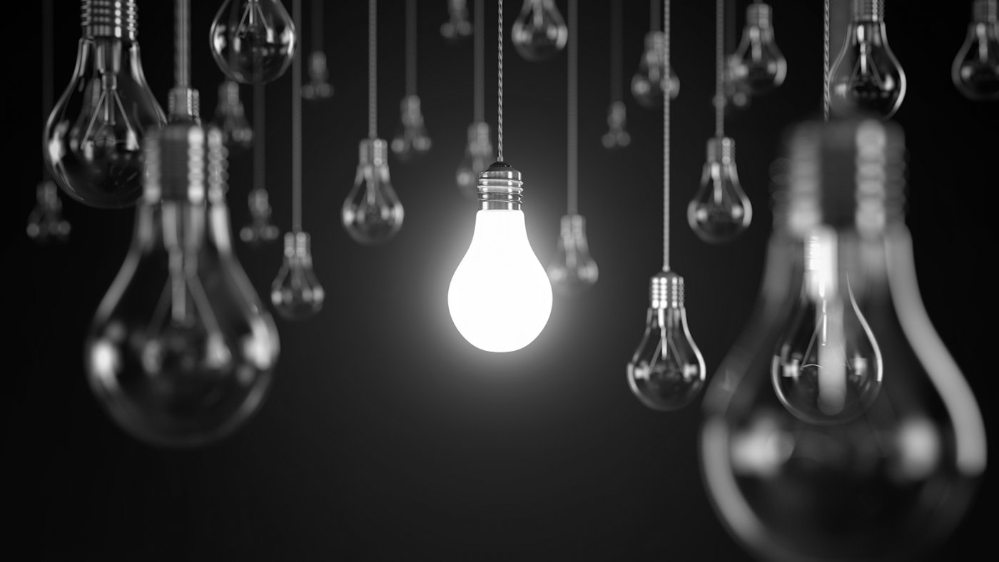 Photograph of light bulbs: central one is lit and surrounded by ones that are off