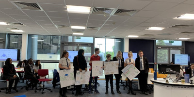 photo of group of secondary school students holding up posters with innovation project ideas on them.
