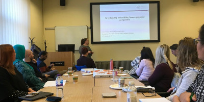 photo of Stacey Mottershaw presenting to a round-table audience.