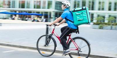 Bike courier with Deliveroo bag on back
