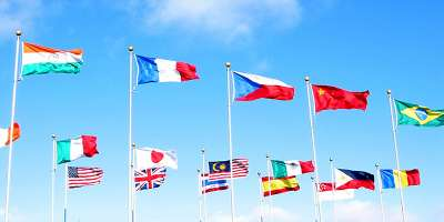 Lots of flags of different colours against a bright blue sky