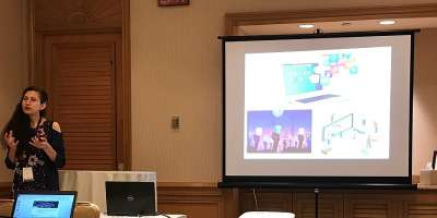 Photograph of Dr Shahla Ghobadi presenting her research in front of a screen.