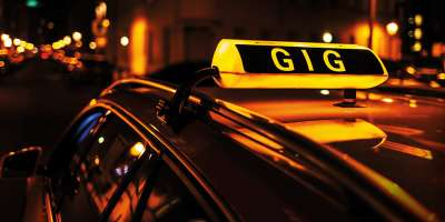 Photograph of a taxi sign atop a car, with the word 'Gig' instead of 'Taxi' being displayed