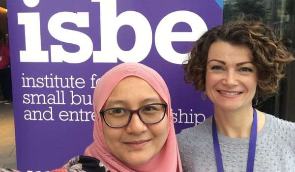 Drs Ainurul Rosli and Isla Kapasi stood in front of an ISBE banner