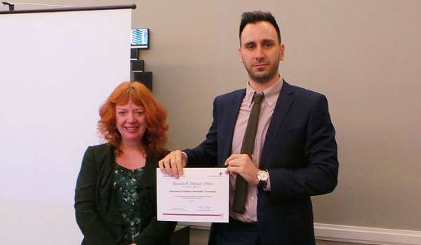 Photograph of Cathy Cassell presenting Aris Theotokis with his award.