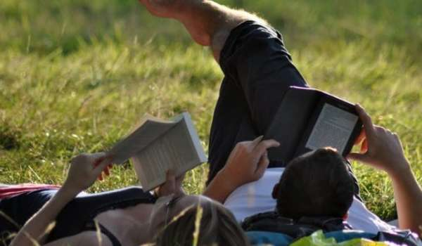 Man and woman relaxing on grass, reading books.