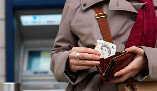Woman placing cash into her purse after withdrawing it from an ATM