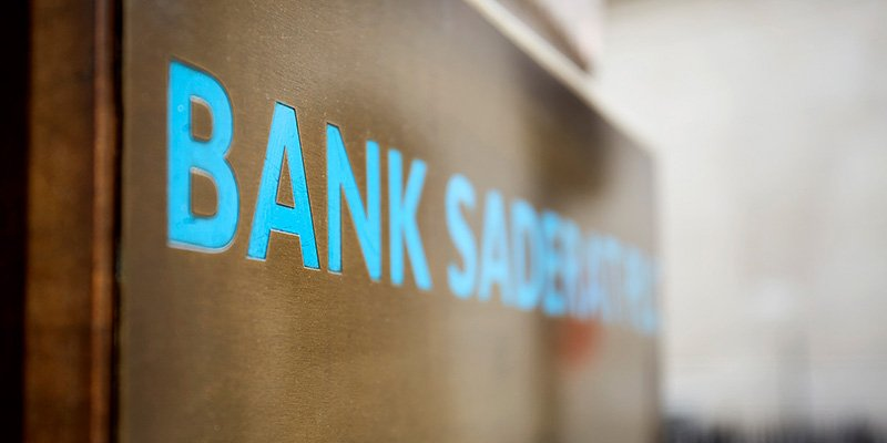 A close up of blue signage saying the word 'BANK'