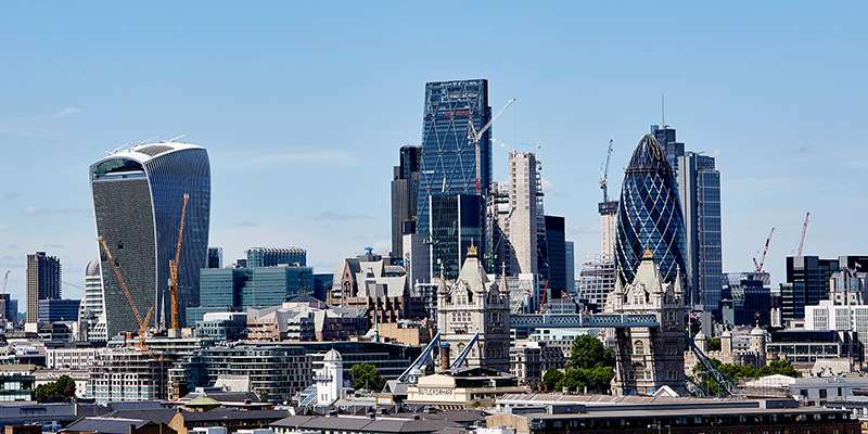 A wide shot of London city skyline against a blue sky