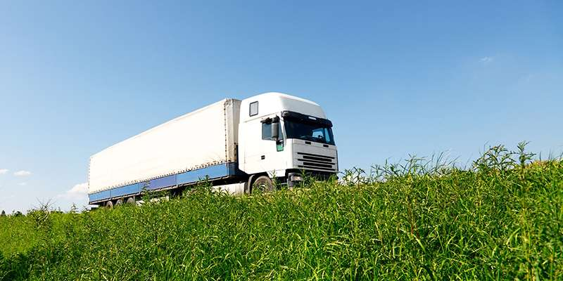 Lorry travelling along a road by grass